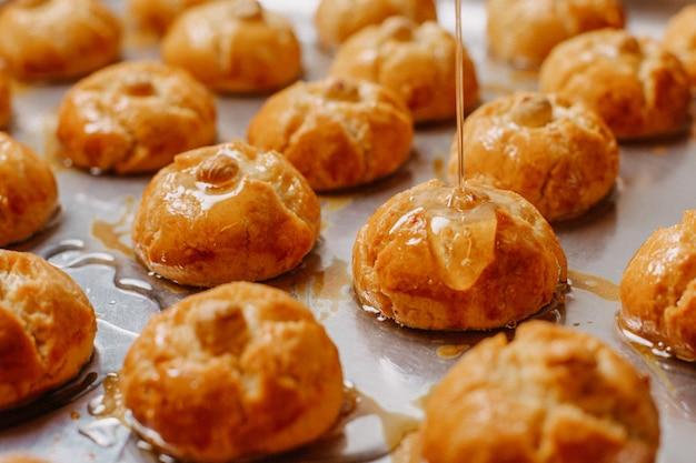 Galletas marrones dulces deliciosas deliciosas vertidas con jarabe dentro de la bandeja del horno