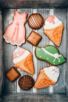 Galletas con masilla de cocina en una caja de madera. galletas redondas y cuadradas. helado en un cono de waffle.