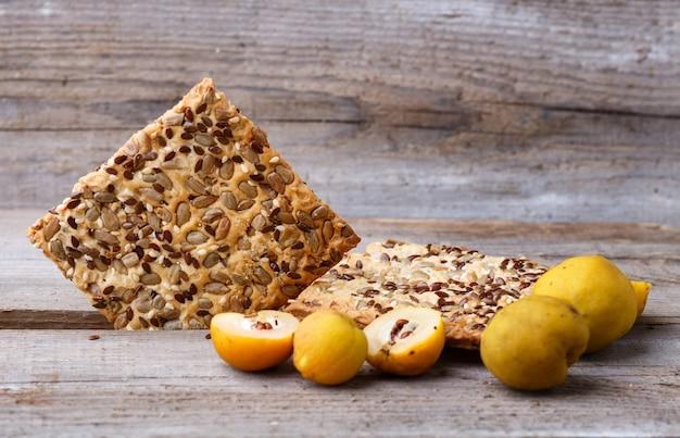 Galletas y membrillo amarillo en madera.