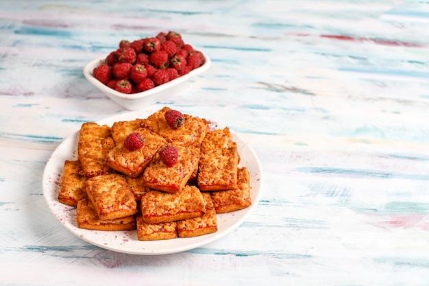 Galletas de mermelada de frambuesa deliciosas dulces con frambuesas maduras, vista superior