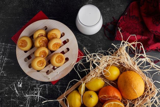 Galletas con mermelada de naranja servidas con un vaso de leche, vista superior.