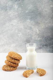 Galletas multicereales con leche fresca colocada sobre un mantel azul.