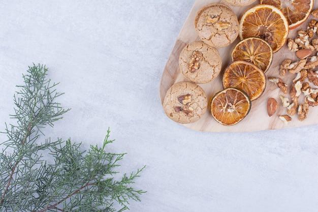 Galletas, naranjas y nueces diversas sobre tabla de madera.