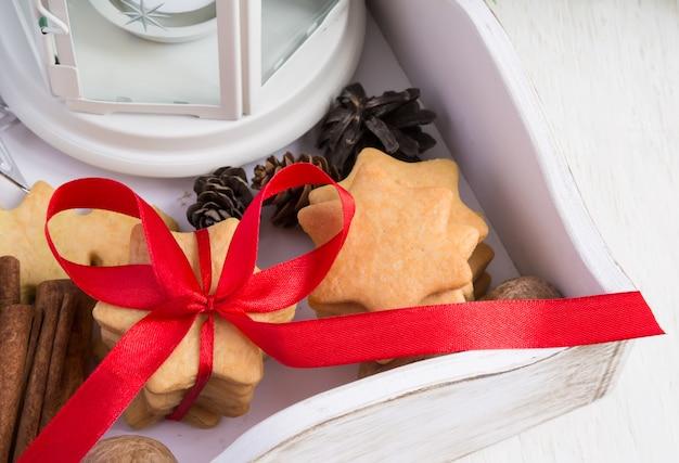 Galletas de navidad atadas con cinta roja en una caja de madera