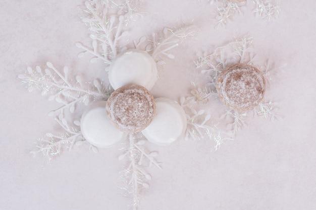 Galletas de navidad con copos de nieve sobre superficie blanca