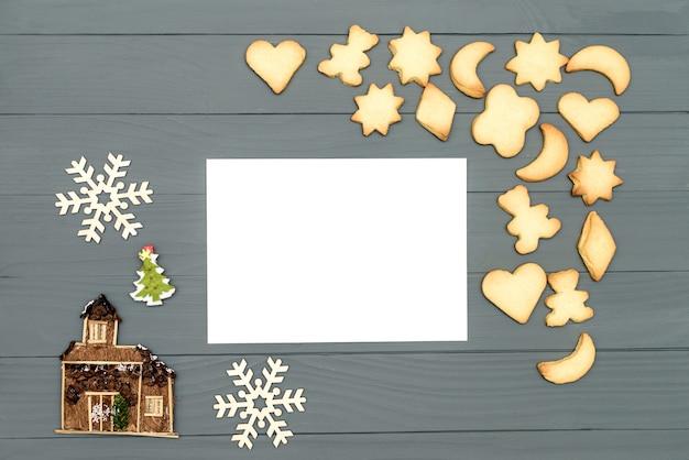 Galletas de navidad en forma de estrella, luna, oso y corazón con canela y copos de nieve decorativos y casa, hoja de papel sobre tabla de madera