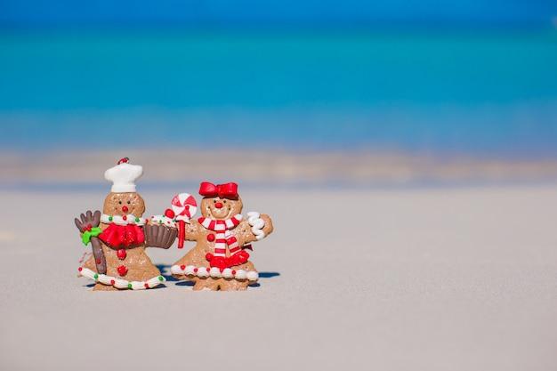 Galletas de navidad hombre de jengibre en una playa de arena blanca