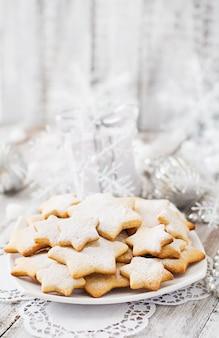 Galletas de navidad y oropel sobre una mesa de madera