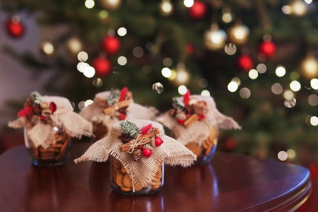 Galletas de navidad de pan de jengibre en el frasco de vidrio. festivo con bokeh y luz. año nuevo y tarjeta de navidad. cuento de hadas mágico