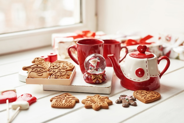 Galletas de navidad y taza de té caliente, navidad. pan de jengibre de navidad, dulces, café en la taza roja en la mesa de madera en la mesa de ventana de día de invierno helado. inicio acogedoras vacaciones. plantilla postal