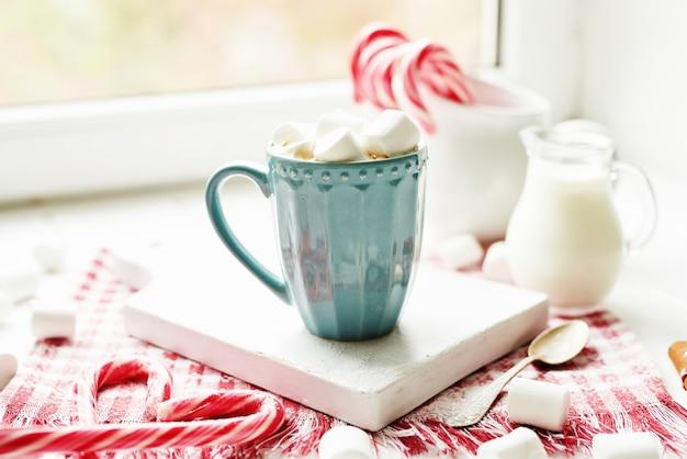 Galletas navideñas, leche, cacao, malvaviscos, dulces en un plato blanco junto a la ventana