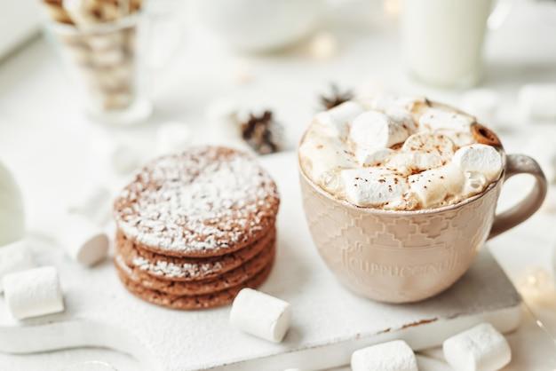 Galletas navideñas, leche, cacao, malvaviscos, merengue en un plato blanco junto a la ventana