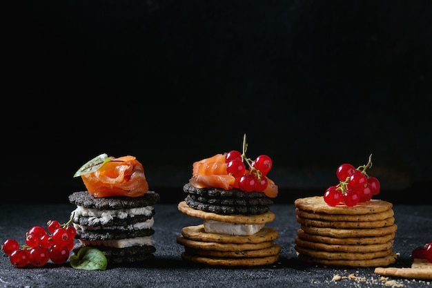 Galletas negras con salmón y bayas.