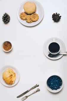 Galletas; un pan; bollo; mermelada; piña; arándanos y taza de café sobre fondo blanco