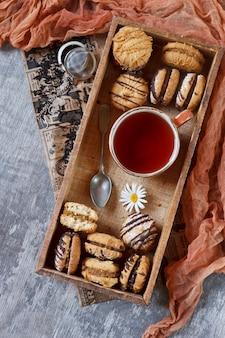 Galletas de pan dulce hechas en casa con un relleno y una taza de té en una caja de madera.