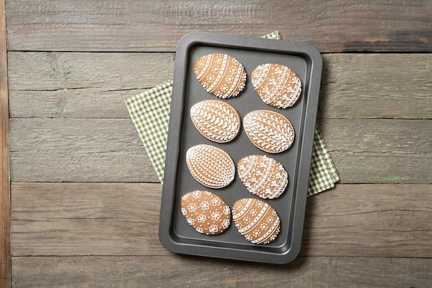 Galletas de pascua en una bandeja para hornear sobre un fondo de madera vieja. huevo de pascua.