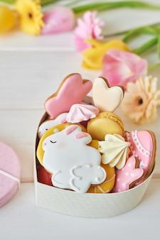 Galletas de pascua en caja con macarons y flores.