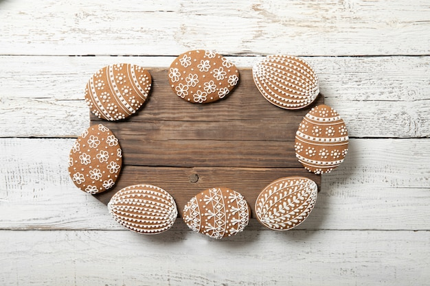 Galletas de pascua sobre un fondo blanco de madera. lugar para el texto. huevos de pascua. en forma de marco.