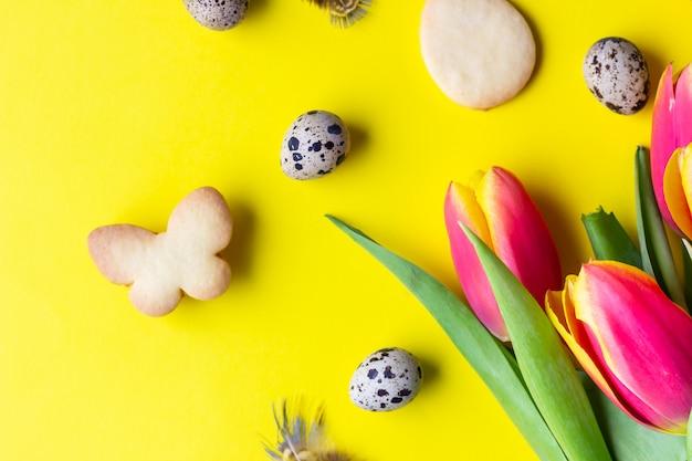 Galletas de pascua, tulipanes rojos y amarillos, huevos de codorniz sobre papel amarillo