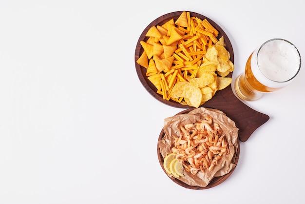 Galletas y patatas fritas con un vaso de cerveza.