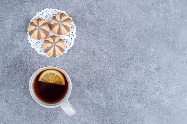 Galletas de patrón de cebra y taza de té en la superficie de mármol