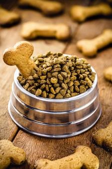 Galletas para perros en forma de hueso con un tarro de comida, snacks para perros en un ambiente rústico, cono para mascotas