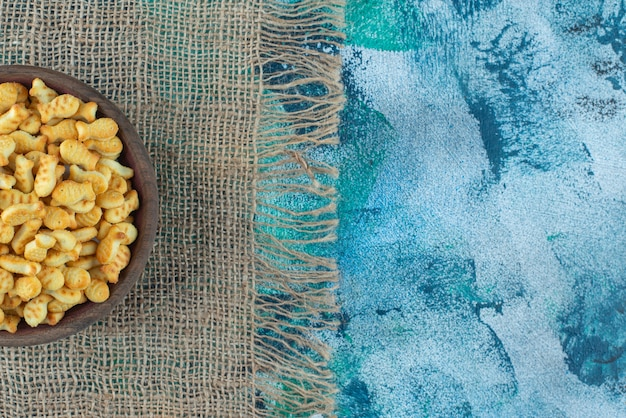 Galletas de pescado en un recipiente sobre textura de mármol.