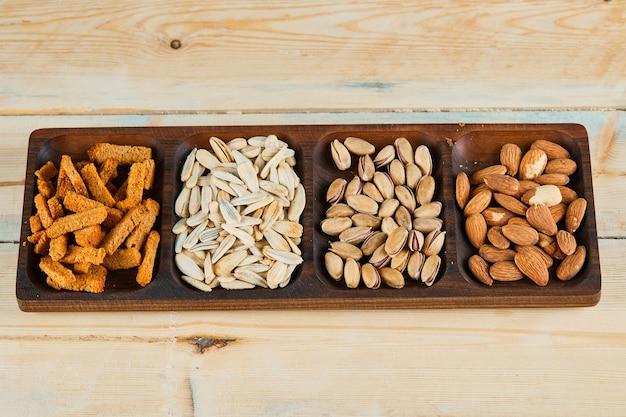 Galletas, pistachos y almendras en bandeja de madera.