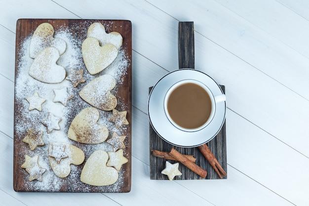 Galletas planas en forma de corazón y estrella sobre tabla de cortar de madera con taza de café, canela sobre fondo de tablero de madera blanca. horizontal