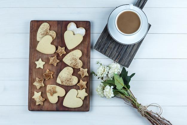Galletas planas en forma de corazón y estrella sobre tabla de cortar de madera con taza de café, flores sobre fondo de tablero de madera blanca. horizontal
