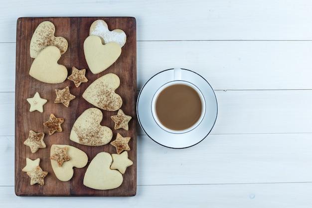 Galletas planas en forma de corazón y estrella sobre tabla de cortar de madera con una taza de café sobre fondo de tablero de madera blanca. horizontal