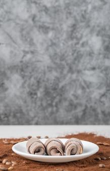 Galletas en plato blanco en polvo de café mezclado.