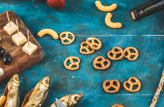 Galletas de pretzel con cubitos de queso en la mesa azul