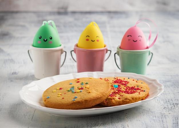 Las galletas de la primavera de pascua adornadas con asperjan en el fondo rústico blanco.