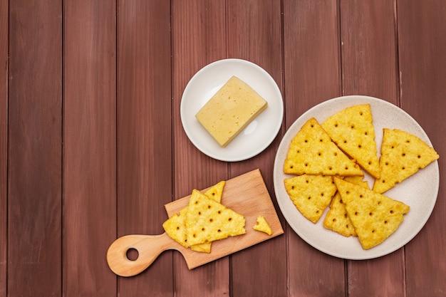 Galletas de queso, concepto de snack salado. galletas, trozo de queso, tabla de cortar.