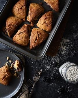 Galletas recién horneadas en una sartén y una galleta a medio comer en un plato sobre una superficie negra