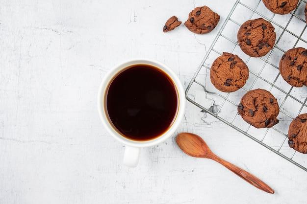 Galletas recién horneadas y tazas de café en la mesa de madera blanca