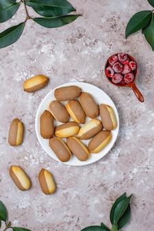 Galletas con relleno de mermelada de frambuesa y frambuesas congeladas sobre fondo claro, vista superior