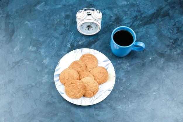 Galletas, reloj despertador y taza de café sobre un fondo azul oscuro