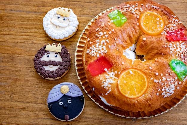 Galletas de los reyes magos junto a un delicioso pastel de navidad español sobre una mesa de madera