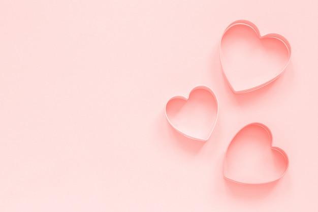 Las galletas rosadas de los cortadores en corazón forman en el fondo del rosa en colores pastel, colar entonado. amor romantico patron