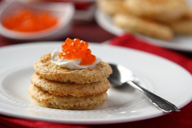 Galletas de salvado de avena con caviar rojo y queso crema