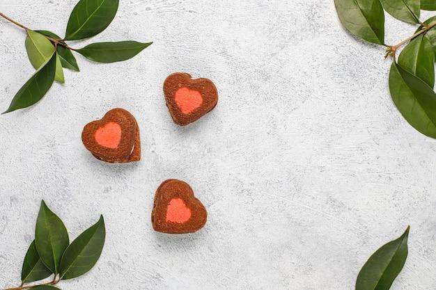 Galletas de san valentín en forma de corazón con frambuesas congeladas sobre fondo claro
