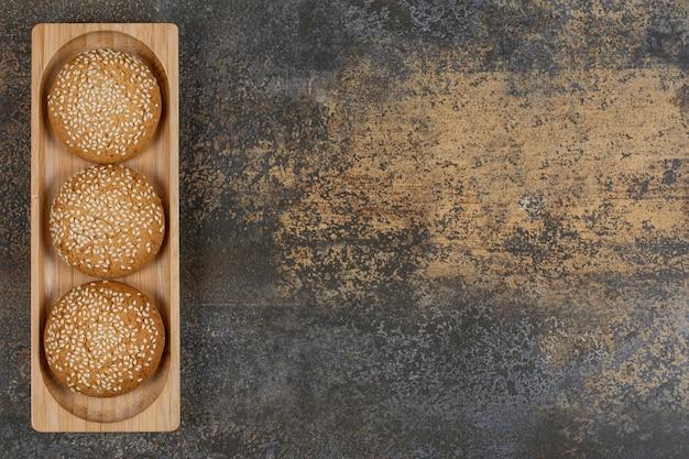 Galletas con semillas de sésamo en placa de madera.