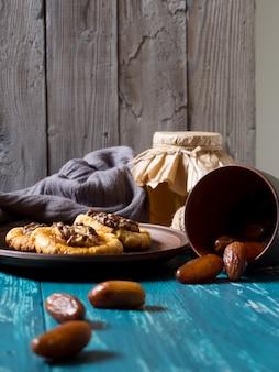 Galletas, un tarro de cristal de miel y dátiles dispersos sobre madera turquesa.
