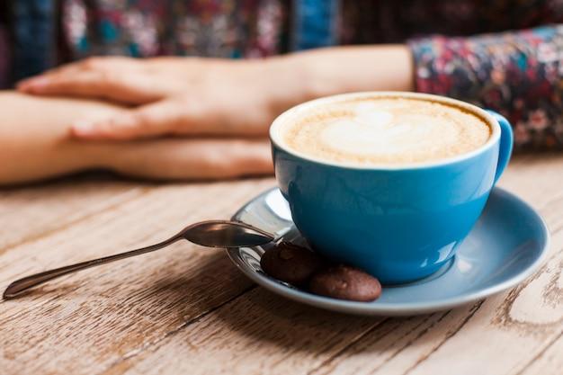 Galletas y taza de café con leche frente a la mujer sentada en la cafetería