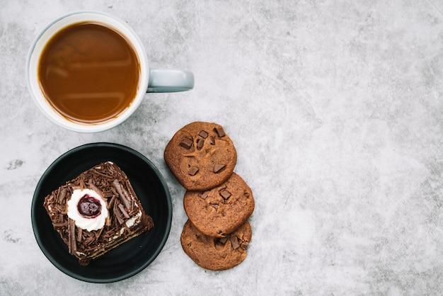 Galletas; taza de café y rebanada de pastel en el fondo
