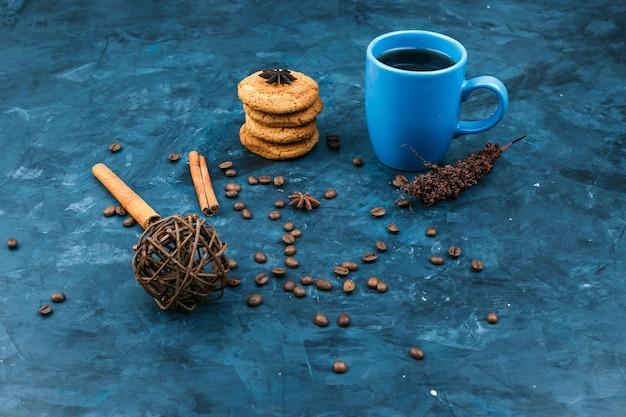 Galletas y taza de café sobre un fondo azul oscuro