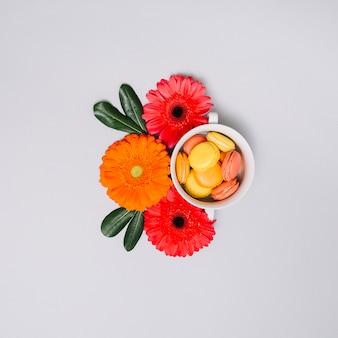 Galletas en taza con capullos de flores en la mesa