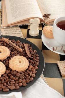 Galletas y una taza de té en un tablero de ajedrez